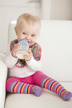 0 1 year: A baby sitting on a sofa with a bottle of milk