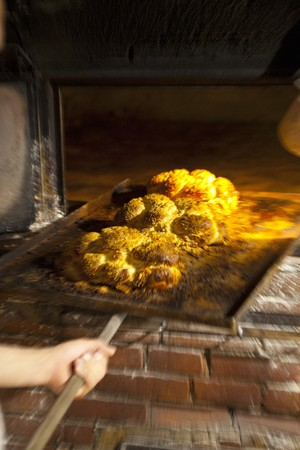 woodfired: Freshly baked bread rolls on a baking tray in a wood-fired oven