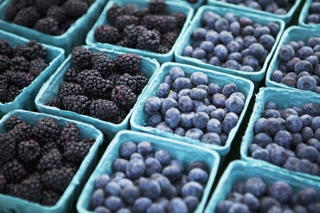 Baskets of Freshly Picked Blueberries and Blackberries at a Farmers Market LANG_EVOIMAGES