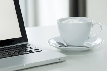 worktable: Cappuccino next to a laptop LANG_EVOIMAGES