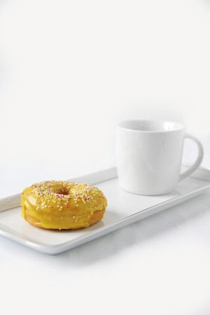 dragees: A doughnut with yellow glaze and sugar balls and a cup