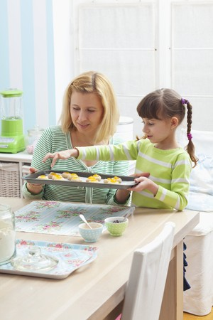 35 to 40 year olds: A mother and daughter holding a baking tray of unbaked jam biscuits