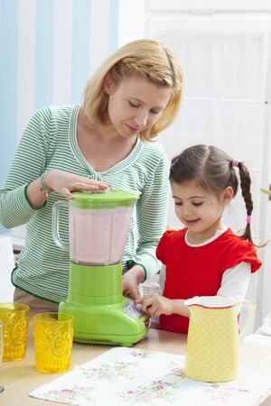 35 to 40 year olds: A mother and daughter preparing a strawberry milkshake