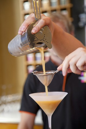 barkeep: A man pouring iced tea from a shaker into a cocktail glass LANG_EVOIMAGES