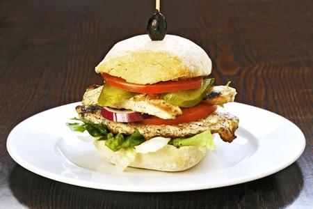 hamburguesa de pollo: Una hamburguesa de pollo con tomate y pepinillos