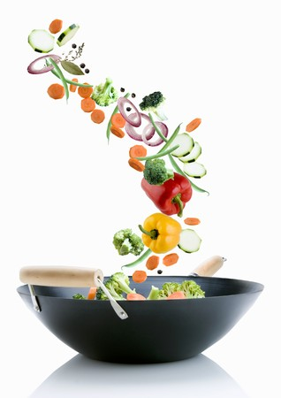falling out: Vegetables falling into a wok