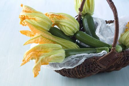 cocozelle: Fresh courgettes with flowers in a basket
