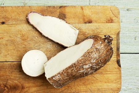 Cassava root, cut open, on a chopping board LANG_EVOIMAGES