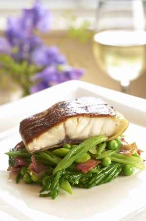 Sea bass fillet on a bed of vegetables with bacon