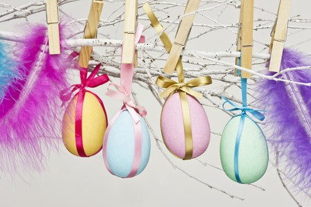 ides: Eggs painted in bright colours for Easter, attached to twigs with clothes pegs LANG_EVOIMAGES