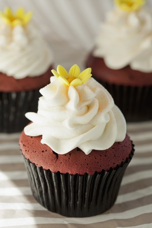 red velvet cupcake: Red Velvet cupcake with cream cheese frosting and a sugar flower, for a wedding
