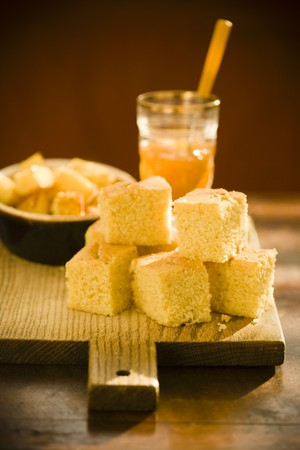 cornbread: Pieces of Cornbread on a Cutting Board with a Jar of Jam LANG_EVOIMAGES