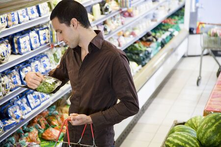 20 to 25 year olds: Man reading the label on food packaging in a supermarket LANG_EVOIMAGES