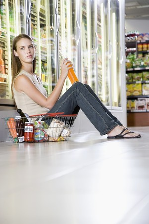 purchased: Woman sitting on a supermarket floor drinking. LANG_EVOIMAGES