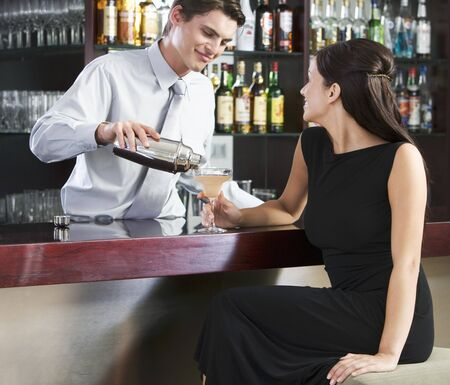 barkeep: A barman pouring a cocktail for a customer