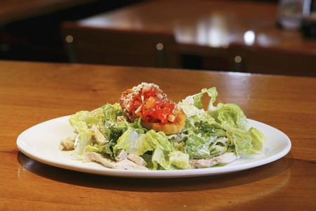 chicken caesar salad: Chicken Caesar Salad on a White Plate LANG_EVOIMAGES