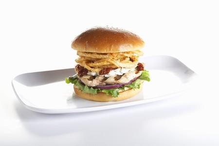 hamburguesa de pollo: Hamburguesa de pollo a la parrilla con cebollas fritas en un bollo