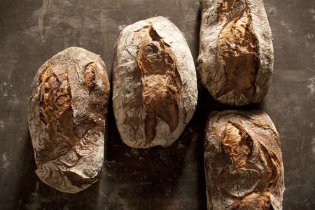 several breads: Four loaves of country bread