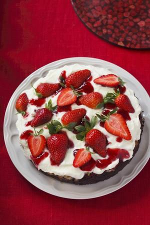 cream on cake: Un pastel de crema con base oscura rematada con fresas en una mesa con un mantel rojo
