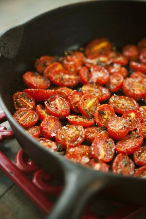 sautee: Halved Cherry Tomatoes Cooked with Salt, Pepper and Rosemary in a Skillet