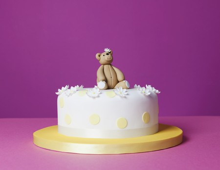 childs birthday party: A teddy bear cake with sugar flowers