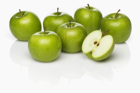 granny smith: Several Granny Smith apples, whole and cut in half