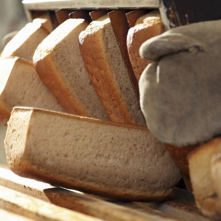 Wheat-rye bread being knocked out of a tin after baking LANG_EVOIMAGES