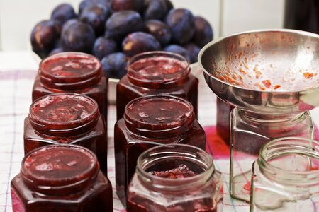 smeared hand: Jars of homemade damson jam