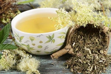 nature cure: A bowl of meadowsweet tea and tea leaves in a tea strainer