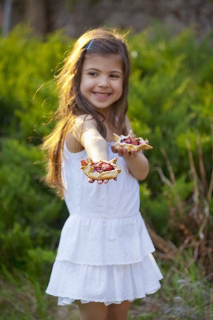 3 4 length: Little girl holding rhubarb tartlets in a garden LANG_EVOIMAGES