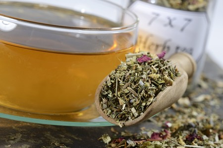 nature cure: A cup of herbal tea and dried herbal tea on a scoop