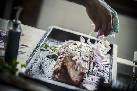 worktops: Onions being added to meat prior to roasting