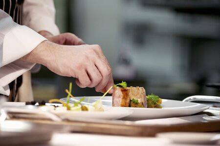 plating: Chef plating up pork dish during service at working restaurant