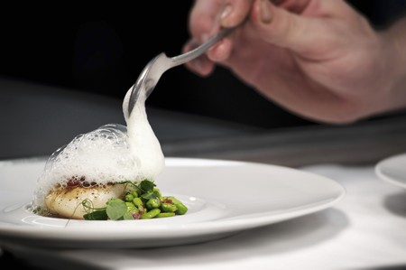 plating: Chef plating up fish and broad bean dish during service at working restaurant