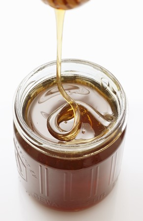 trickling: Honey trickling from a honey dipper into a jar