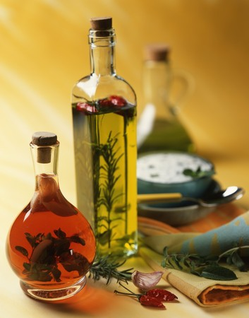 flavoured: Flavoured oil and vinegar in bottles; a bowl of herb sauce in the background