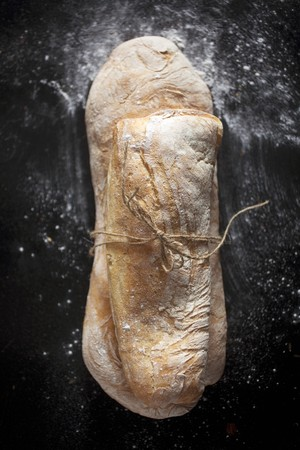 string together: Two ciabatta rolls tied together with string (view from above) LANG_EVOIMAGES