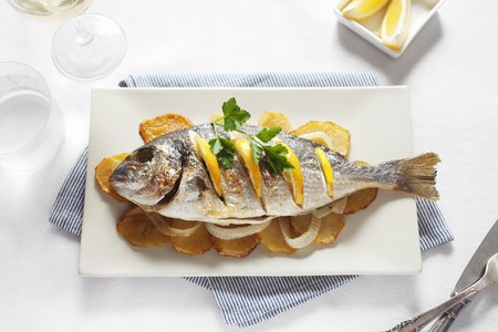 gilthead bream: Grilled gilt-head bream with oranges on top of potato slices
