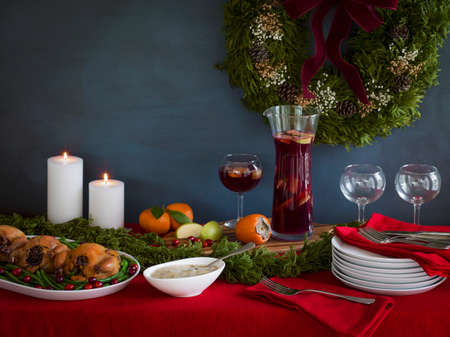 hem: Holiday meal ready for serving with cornish game hens on a bed of green beans and cranberries, gravy and red sangria with stacked plates on a red tablecloth with white candles and a wreath in the background