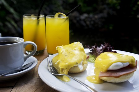 open topped: Eggs Benedict with ham served with coffee and juice on a table outside
