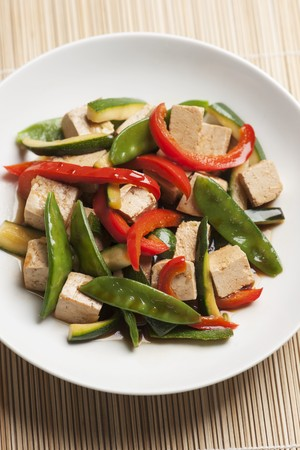 sweet sugar snap: Stir-fried tofu cubes and vegetables (mange tout, courgette and red peppers) with soy sauce