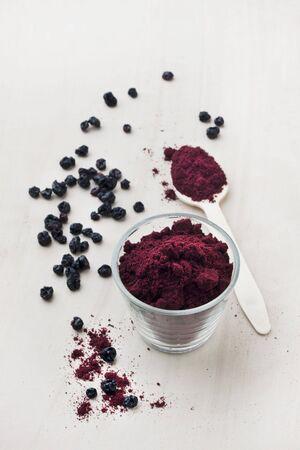 freeze dried: Polvo de la fruta de la grosella negra en un vaso y una cuchara