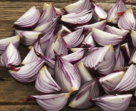 quartered: Quartered onions on a wooden surface