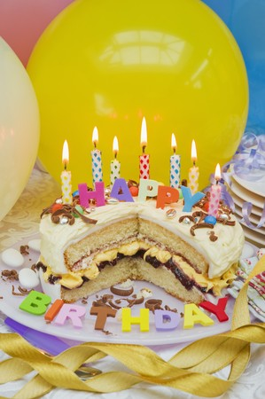 childs birthday party: Sponge layer cake with candles for a birthday, and balloons