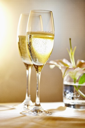 champers: Two glasses of champagne in front of a vase of flowers