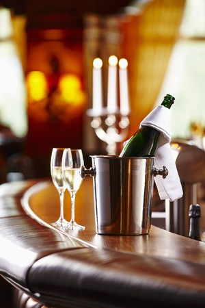 champers: A bottle of champagne and champagne glasses on a bar