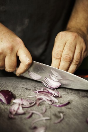 worktops: A man cutting a red onion