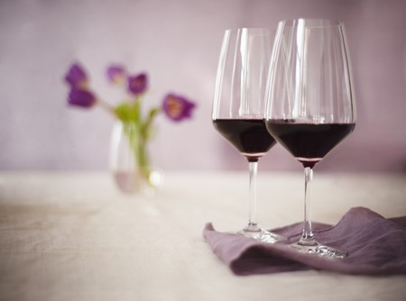twos: Two Glasses of Burgundy Wine With Purple Flowers in the Background