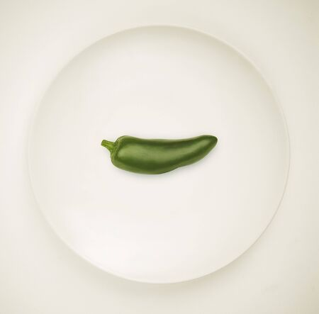 jalapeno pepper: A Green Jalapeno Pepper on a White Plate; White Background LANG_EVOIMAGES