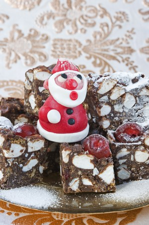 rocky road: a model in red marzipan of father Christmas standing on squares of rocky -road cakes for Christmas with gold patterened paper LANG_EVOIMAGES